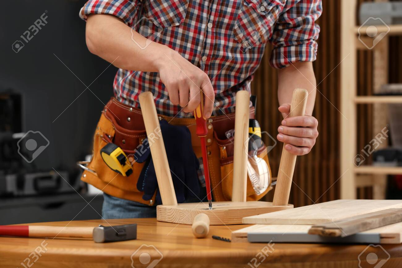 Amazing Young Working Man Repairing Wooden Stool Using Screwdriver Indoors Ocoug Best Dining Table And Chair Ideas Images Ocougorg