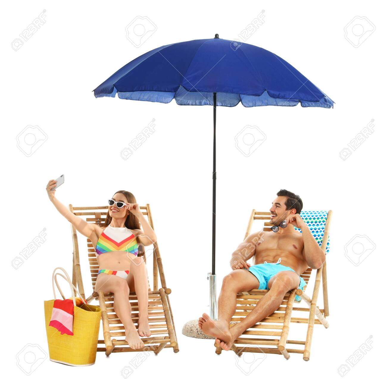 Young couple taking selfie on sun loungers under umbrella against white background. Beach accessories - 128057620