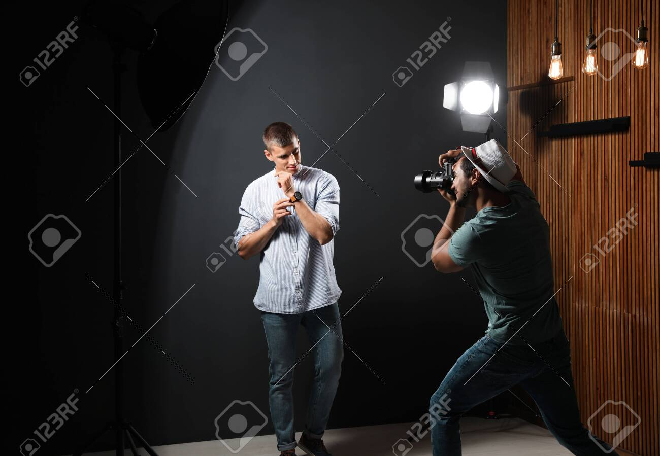Professional photographer taking picture of young man on dark grey background in modern studio - 128520422