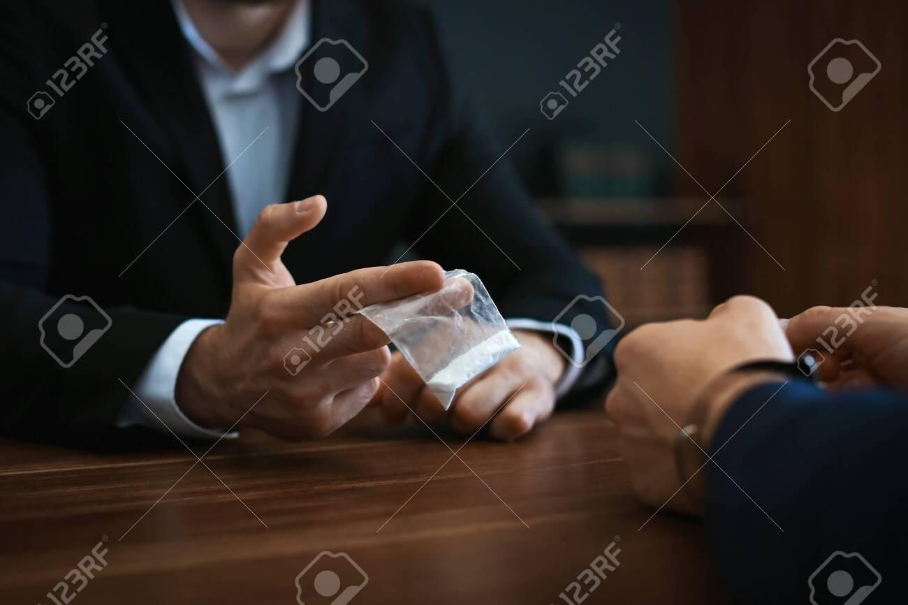 Police officer interrogating drug dealer in handcuffs at desk
