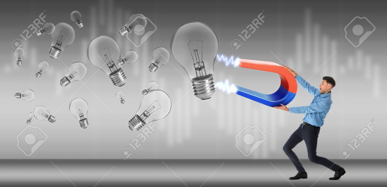 Man Attracting Ideas In Form Of Light Bulbs With Magnet On Grey Stock Photo Picture And Royalty Free Image Image 128528400
