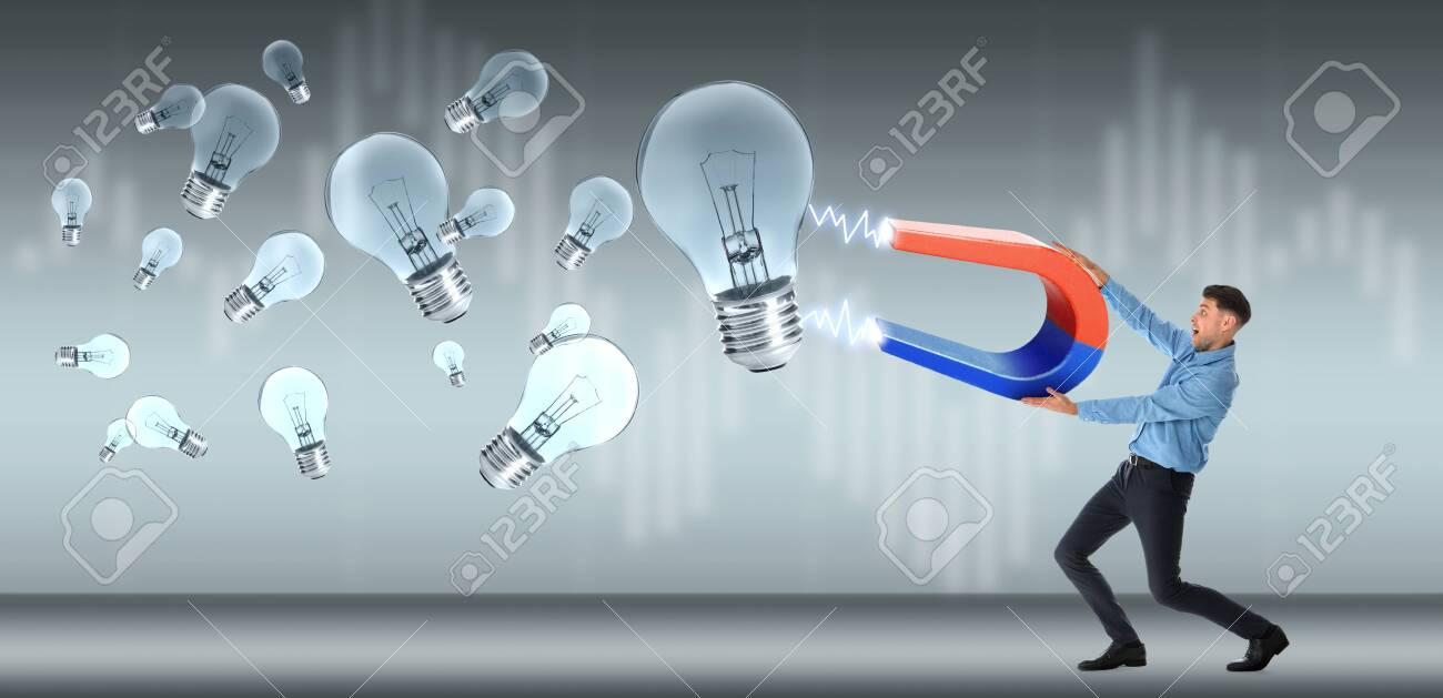 Man Attracting Ideas In Form Of Light Bulbs With Magnet On Grey Stock Photo Picture And Royalty Free Image Image 128528673