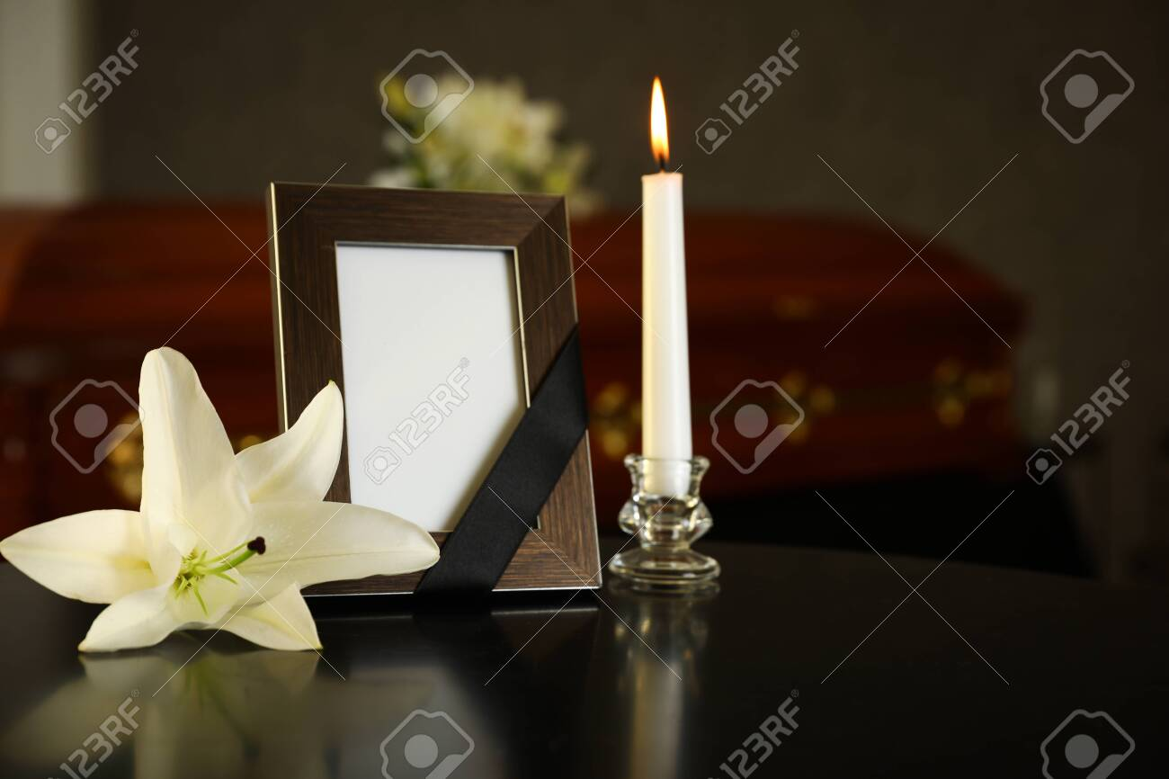 Black photo frame with burning candle and white lily on table in funeral home - 128458331