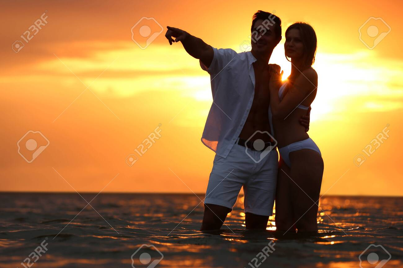 Happy young couple spending time together on sea beach at sunset - 128645596