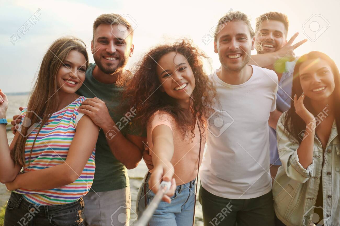 Happy young people taking selfie outdoors on sunny day - 128827359