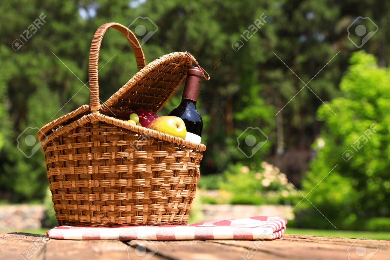 Picnic basket with fruits, bottle of wine and checkered blanket on wooden table in garden - 128780373