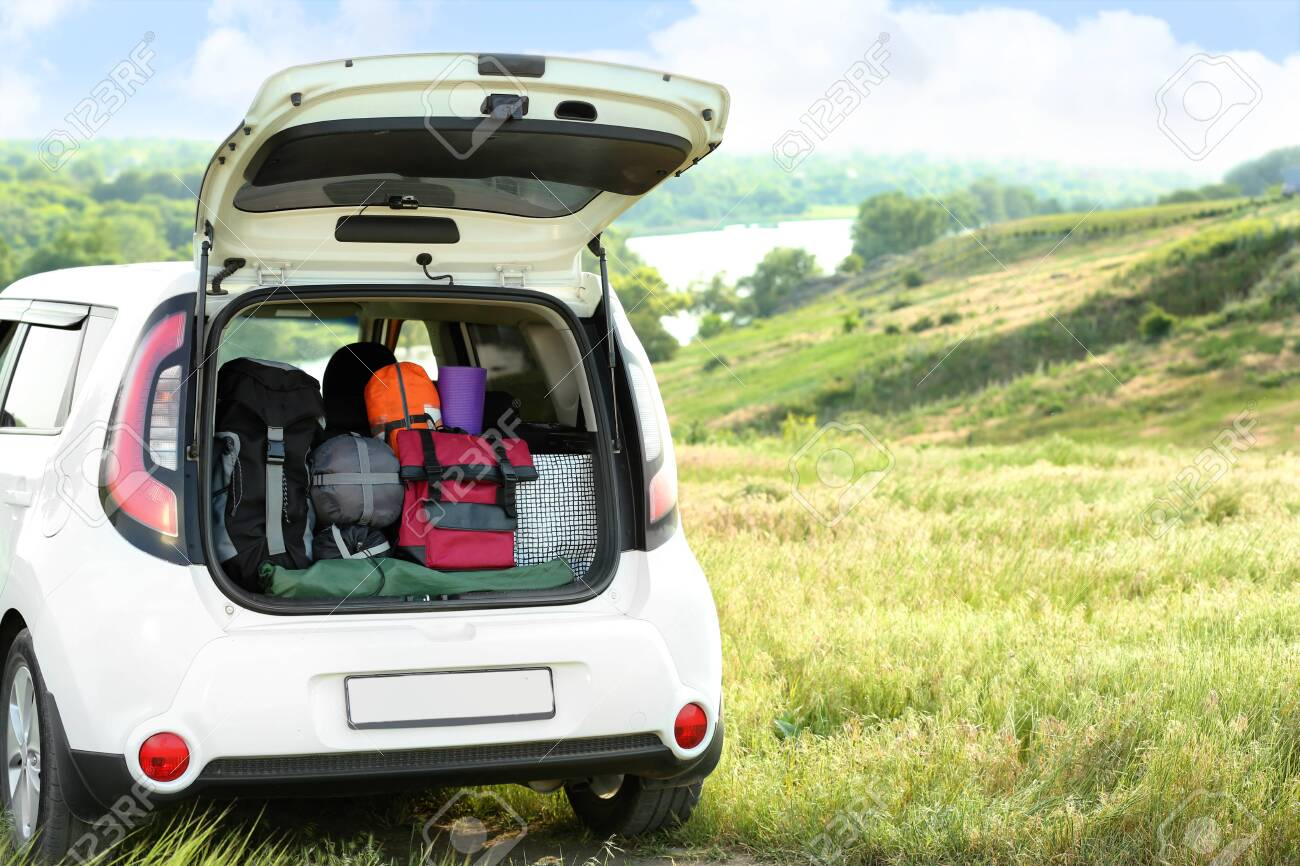 Car with camping equipment in trunk on green field. Space for text - 128780941