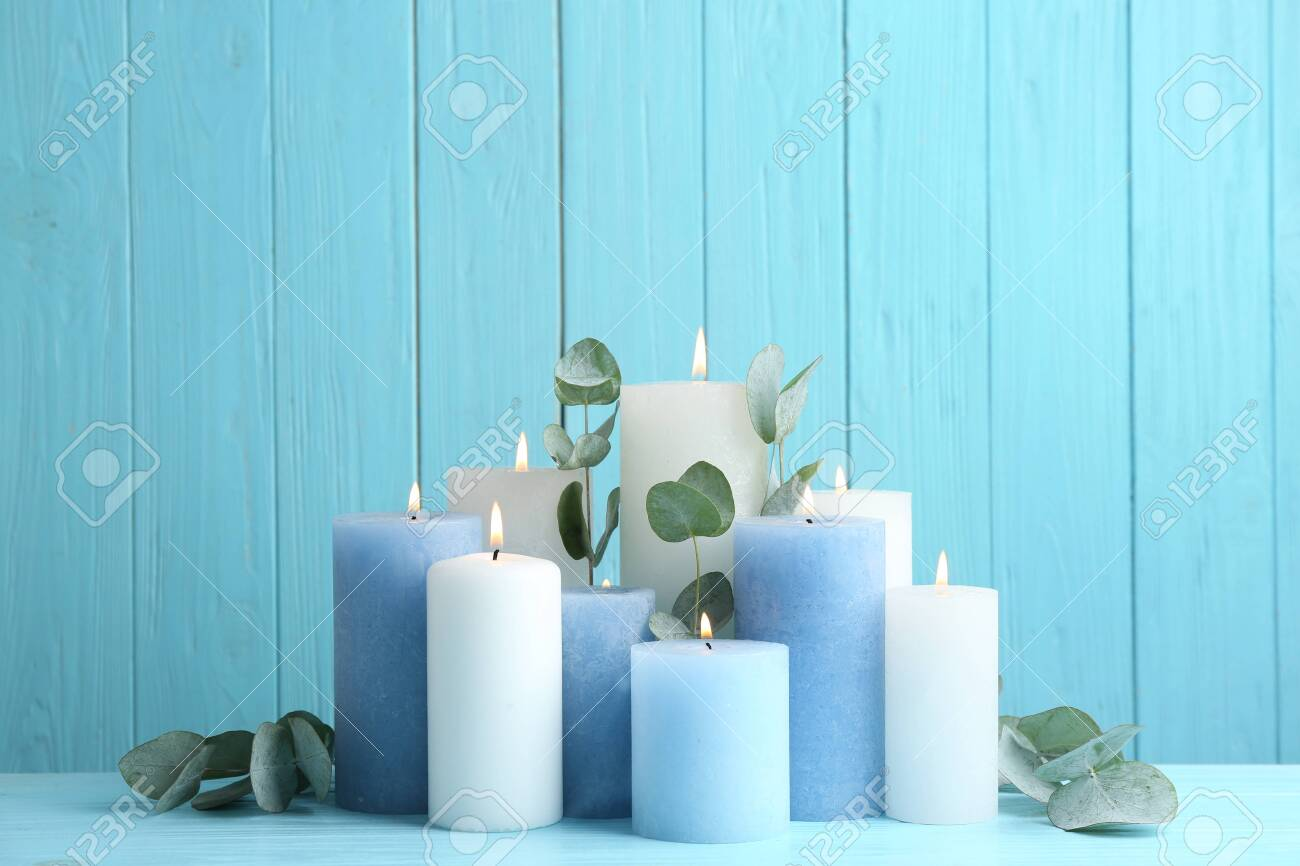 Set of burning candles with eucalyptus on table against light blue wooden background - 128827498
