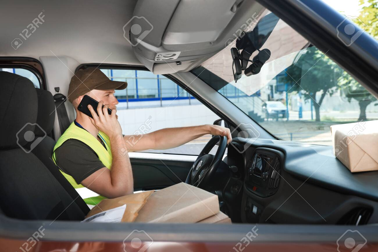 Young courier talking on phone in delivery car - 129708869