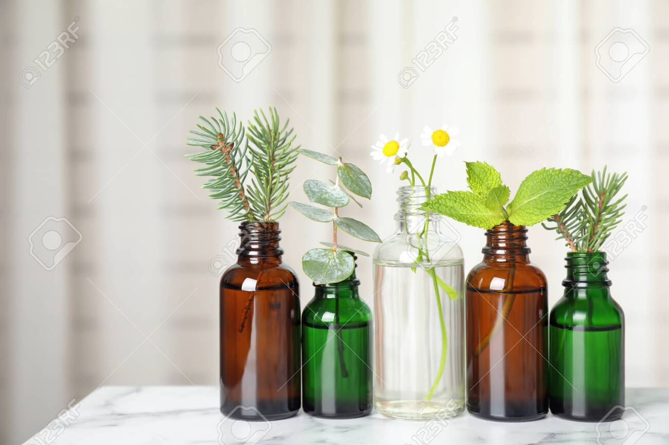 Glass bottles of different essential oils with plants on table - 129386936