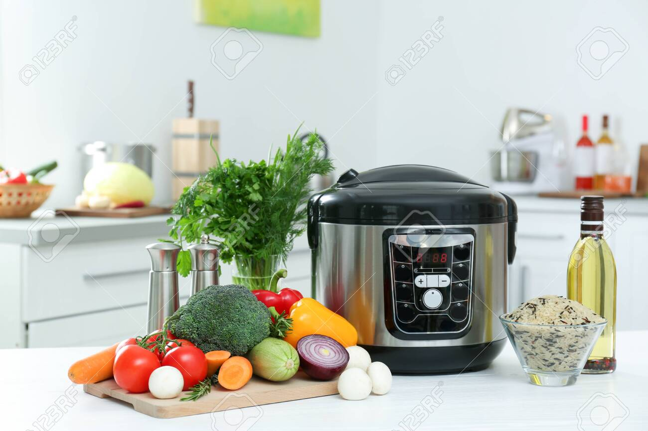 Modern multi cooker and products on kitchen table - 129421183