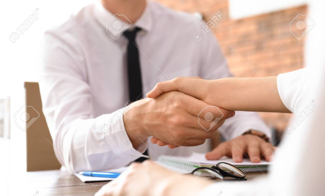 Business partners shaking hands at table after meeting in office, closeup - 129422137