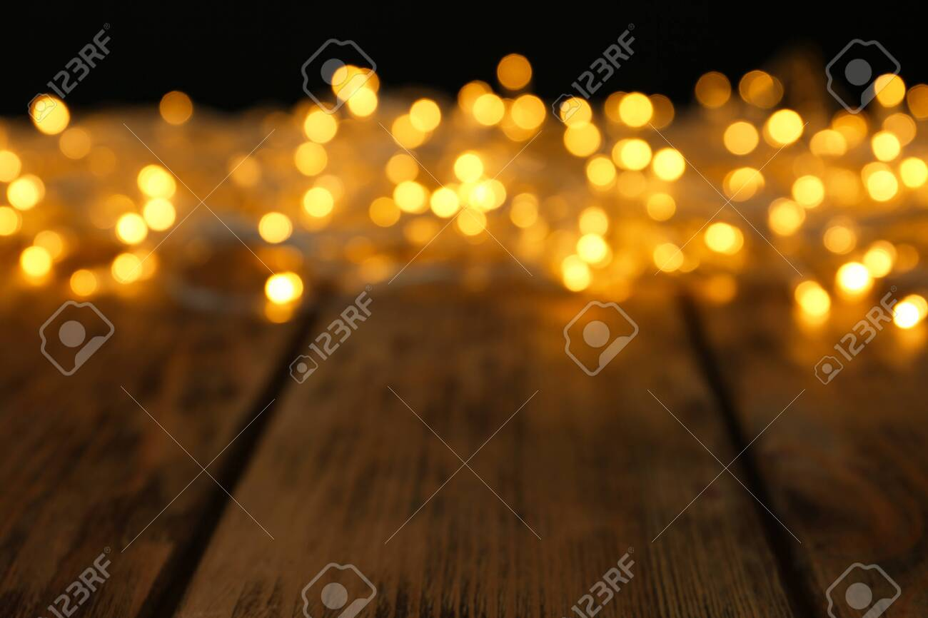 Blurred view of glowing Christmas lights on wooden table - 129524499