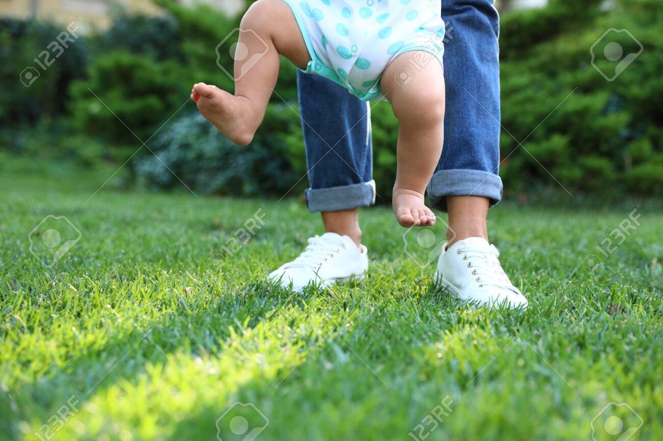 Cute little baby learning to walk with his nanny on green grass outdoors, closeup - 129798725