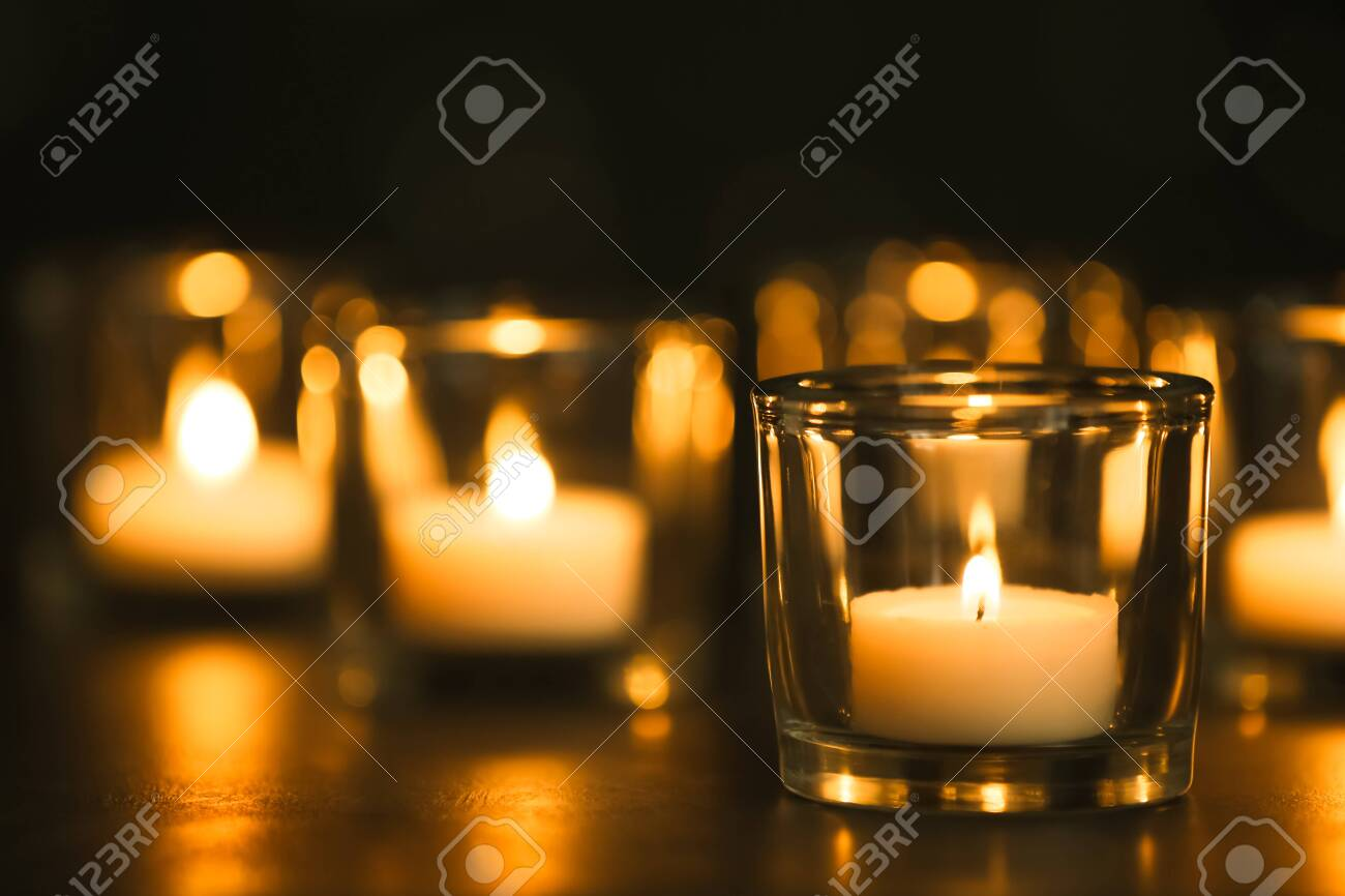 Burning candles on table in darkness. Funeral symbol - 129907351