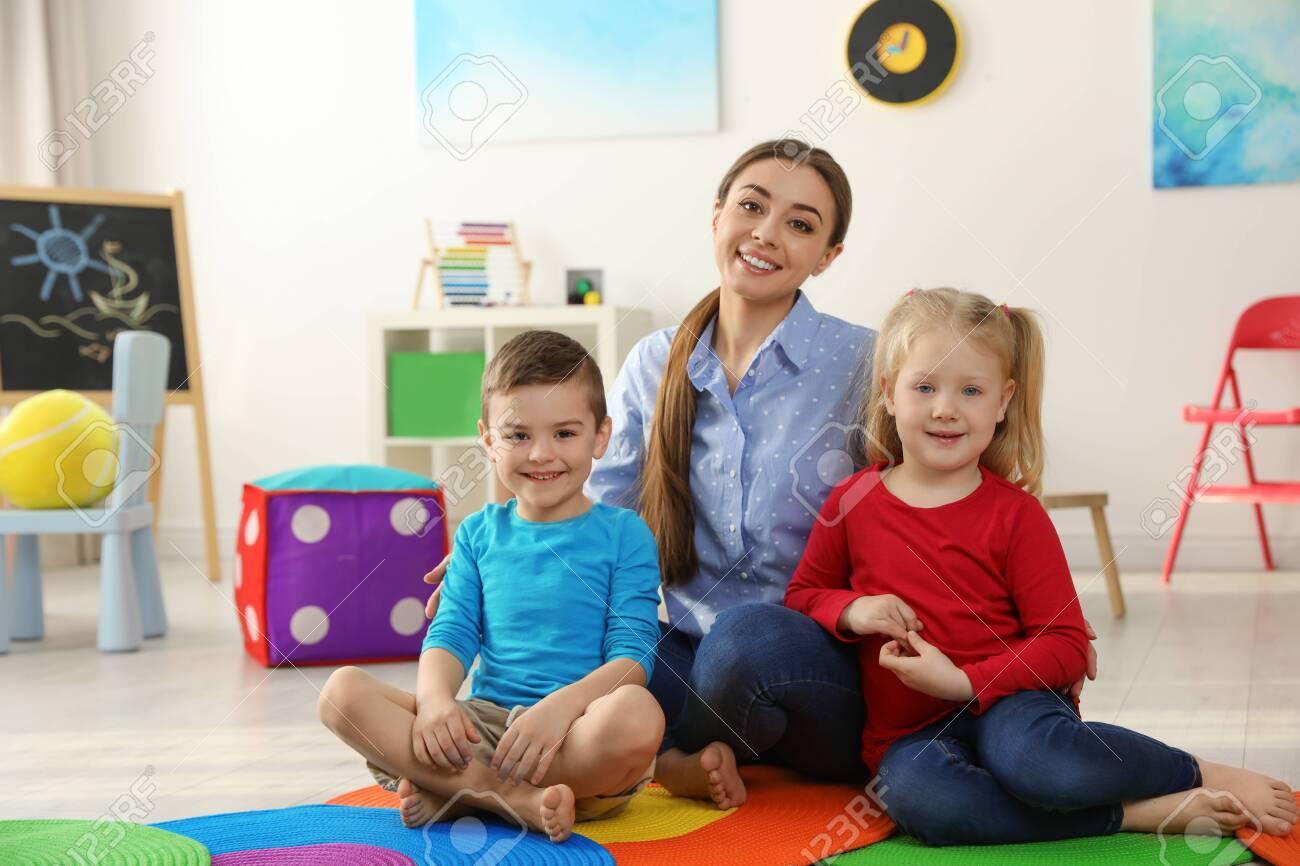 Kindergarten teacher with children in playroom. Indoor activity - 130340403