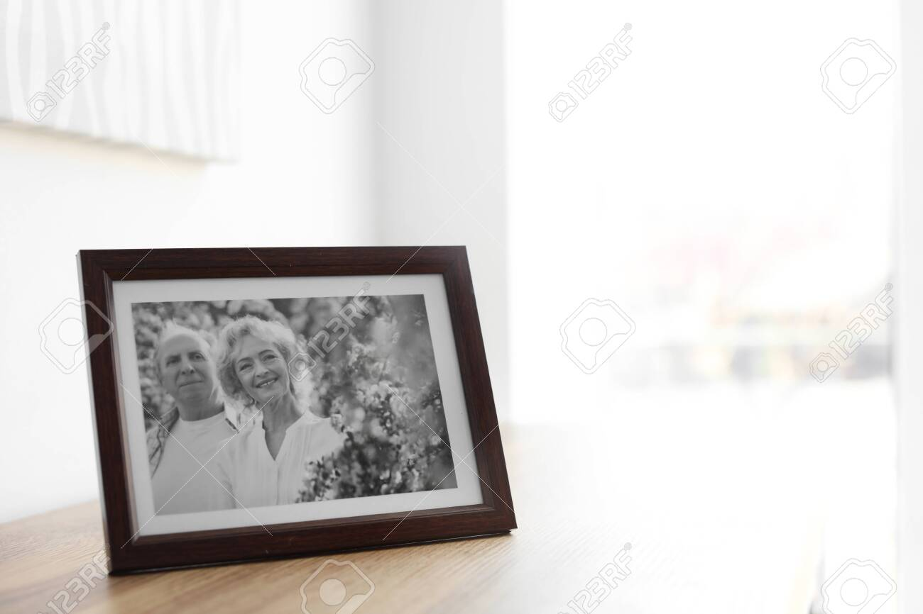 Portrait of senior couple in frame on table indoors. Space for text - 132310477