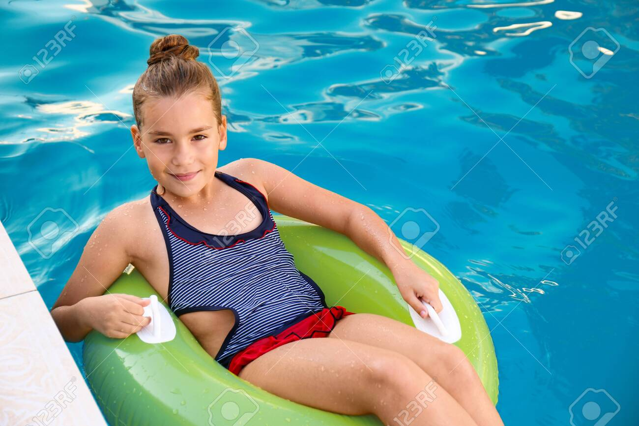 Happy little girl on inflatable ring in swimming pool - 129993972