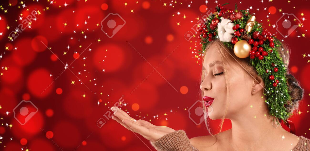 Beautiful young woman with Christmas wreath blowing magical snowy dust on red background. Bokeh effect - 129994073