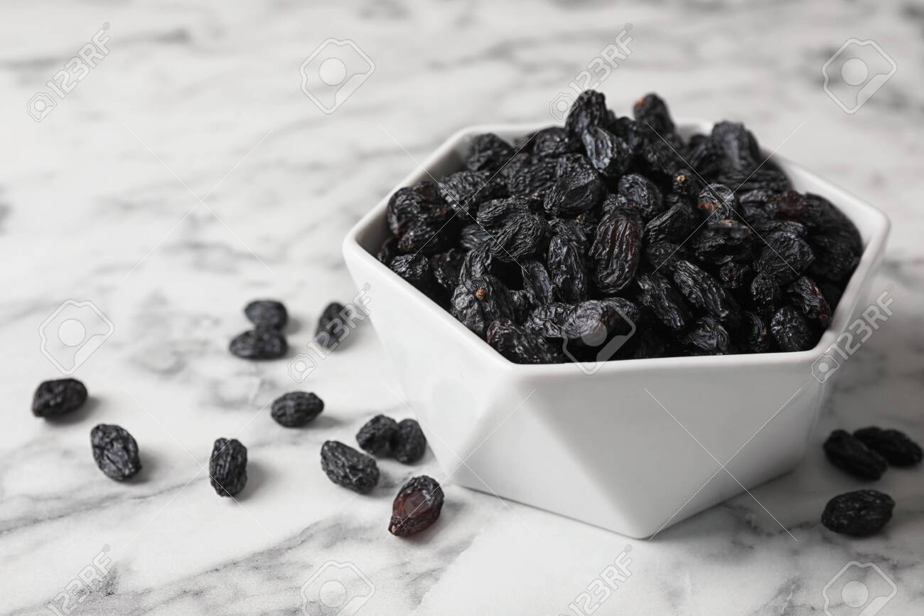 Bowl with raisins on marble table. Dried fruit as healthy snack - 130054528
