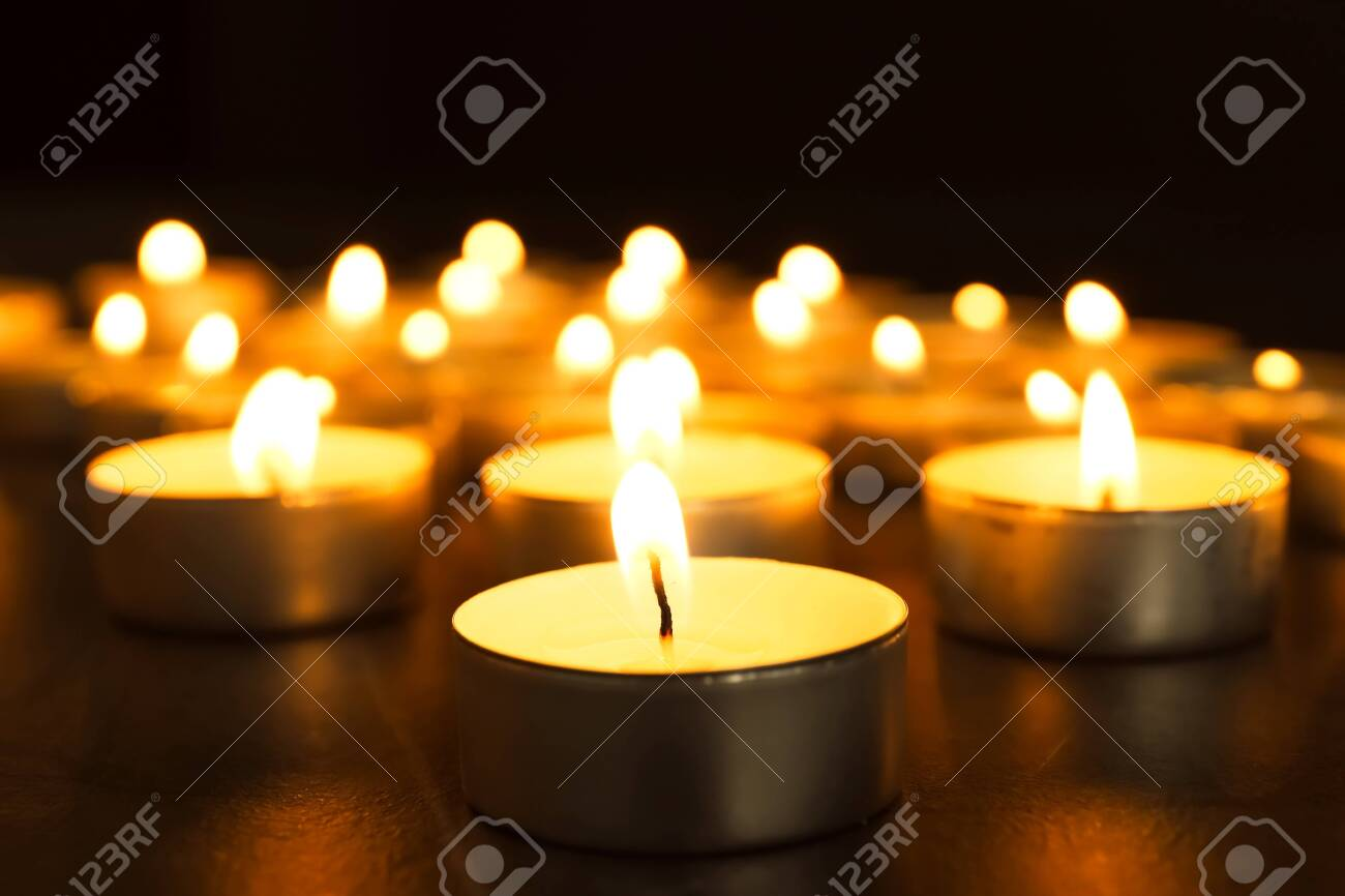 Burning candles on table in darkness, closeup. Funeral symbol - 130396694