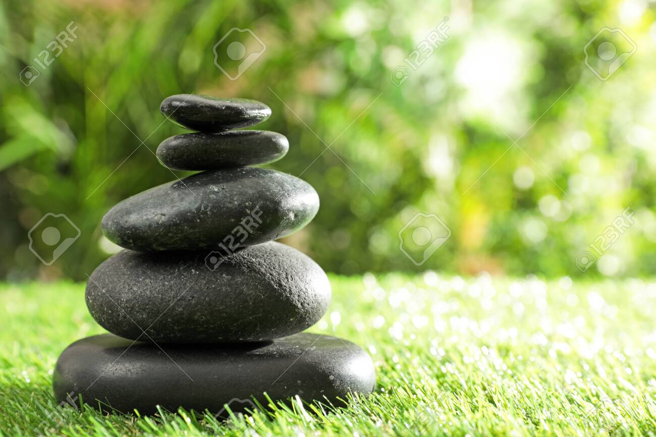 Stack of stones on green grass against blurred background, space for text. Zen concept - 130624022