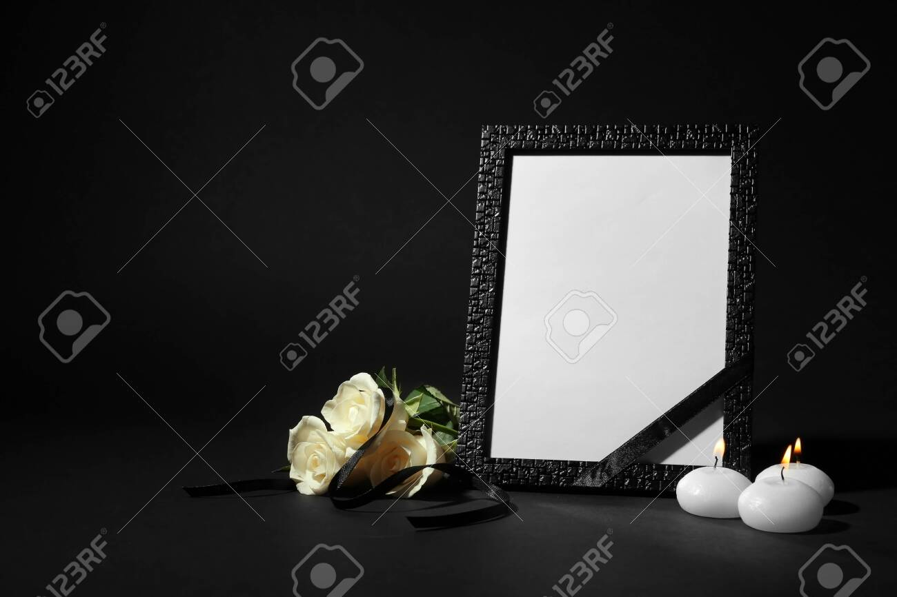 Funeral photo frame with ribbon, white roses and candles on black background. Space for design - 131671249
