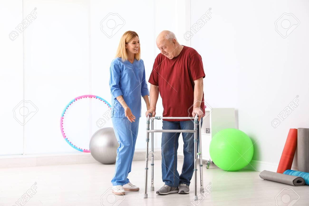Caretaker helping elderly man with walking frame indoors - 132555672