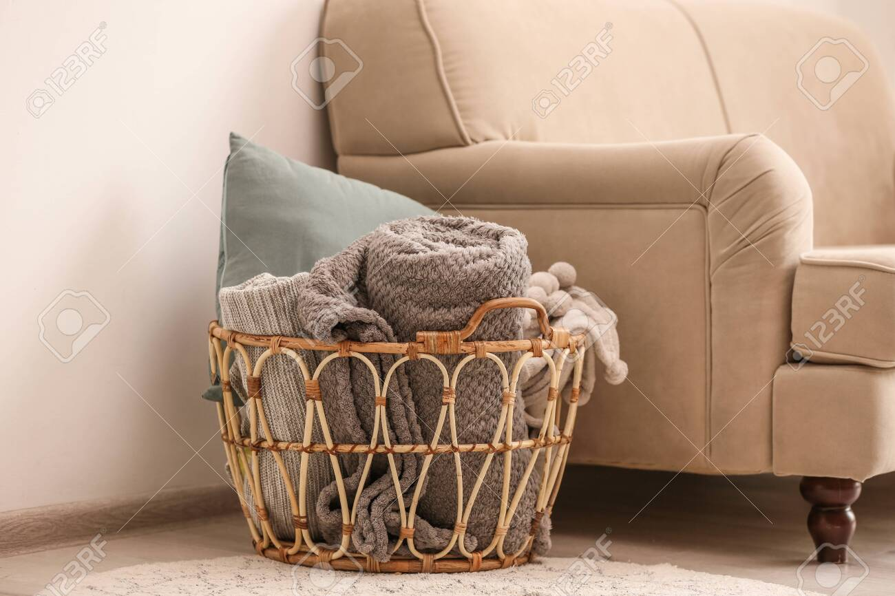 Wicker Basket With Rolled Blankets And Pillow Near Beige Sofa Stock Photo Picture And Royalty Free Image Image 131456228