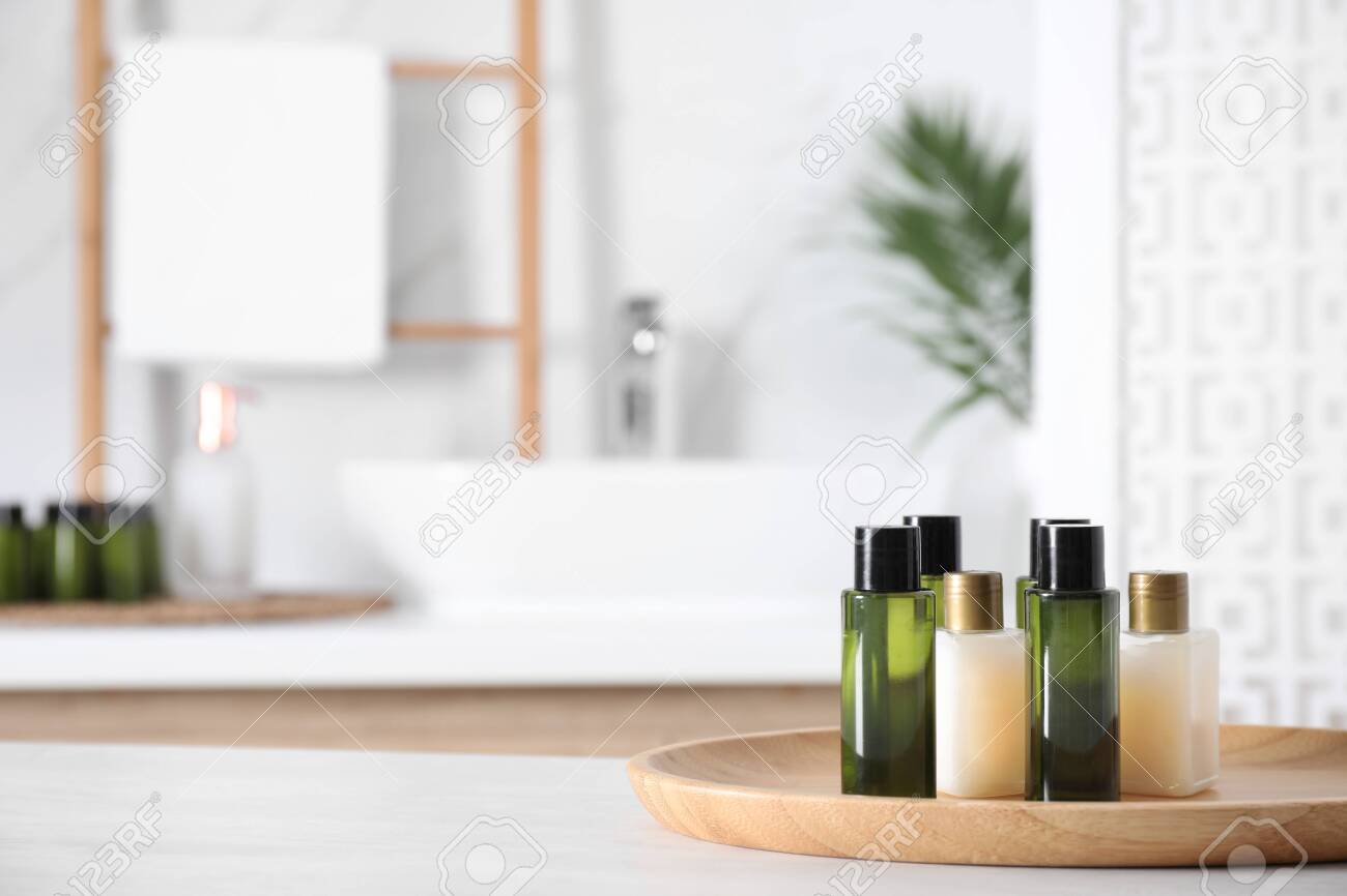 Wooden tray with mini bottles of cosmetic products on white table in bathroom. Space for text - 131683973