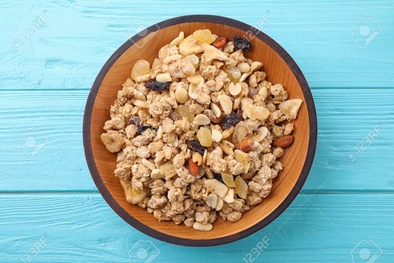 Bowl with healthy granola on light blue wooden table, top view - 131677800