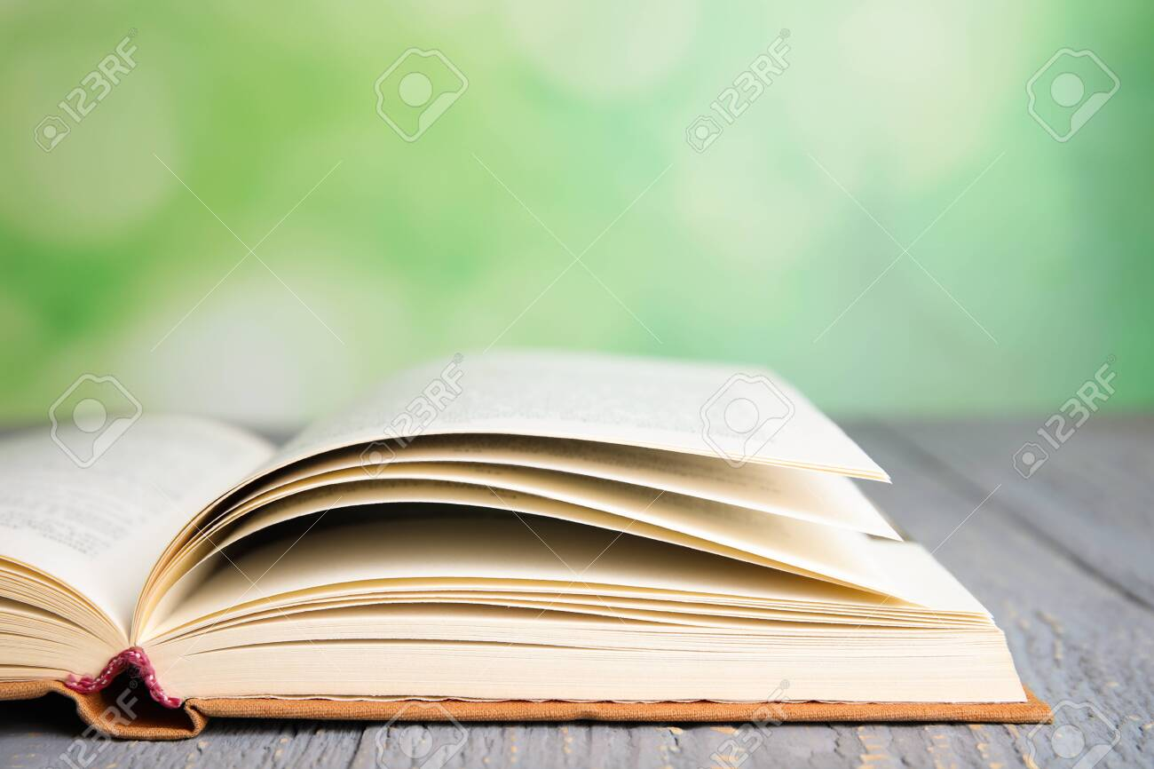 Open book on grey wooden table against blurred green background, closeup. Space for text - 131818687