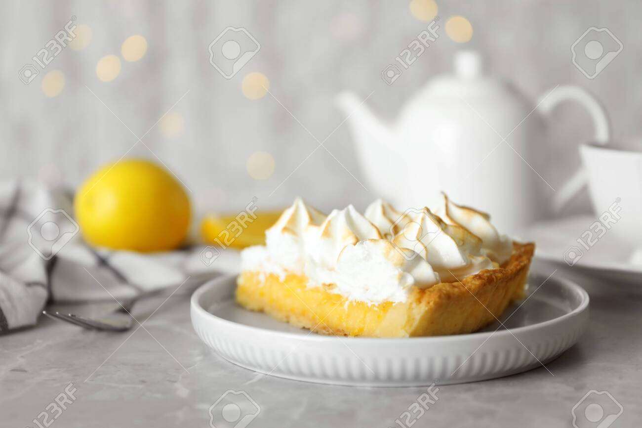 Plate with piece of delicious lemon meringue pie on light grey table - 132474723