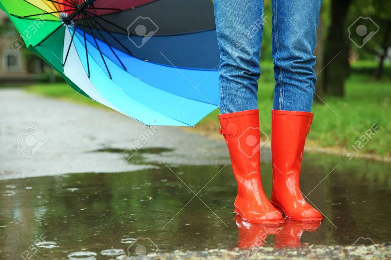 Woman with umbrella and rubber boots in puddle, closeup. Rainy weather - 132602941