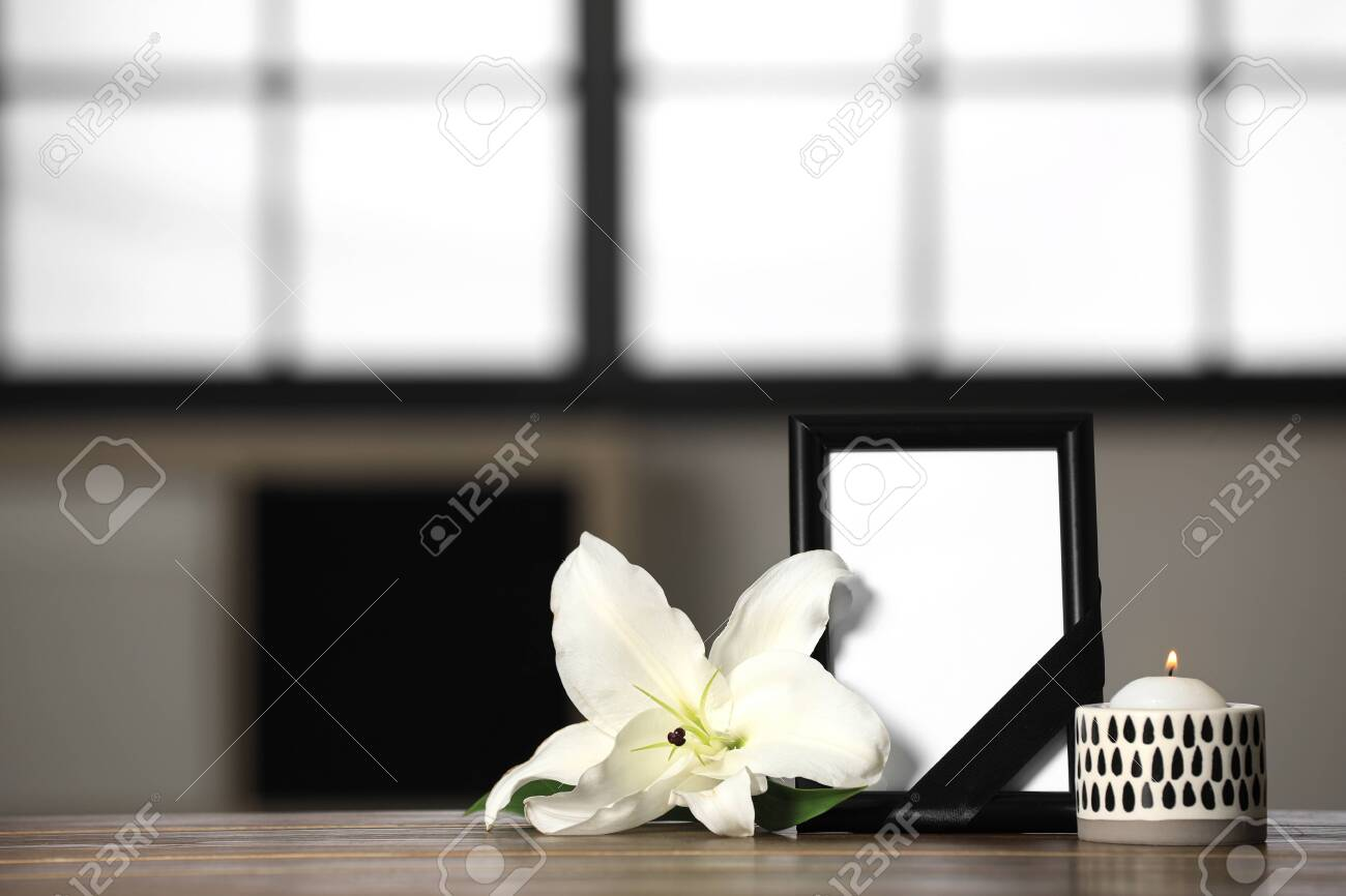 Funeral photo frame with black ribbon, lily and candle on wooden table indoors. Space for design - 132634268