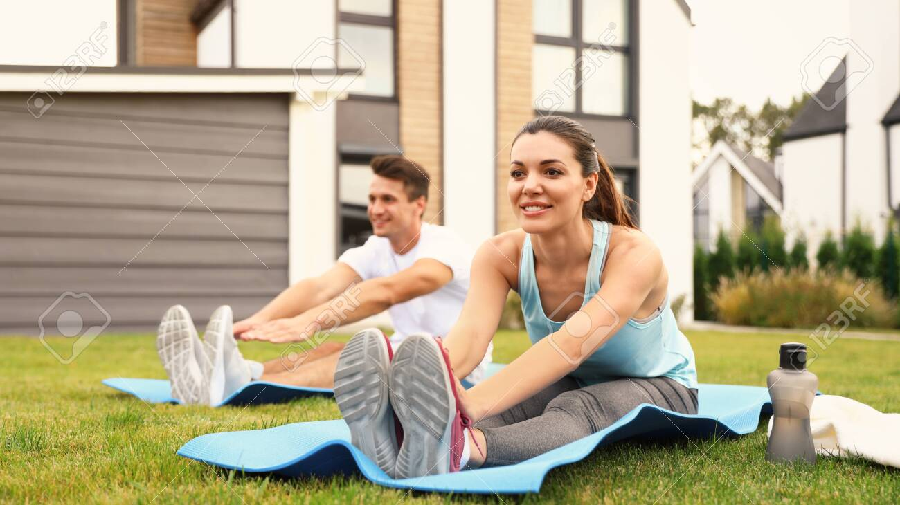 Sporty couple practicing morning yoga at backyard. Healthy lifestyle - 134105404