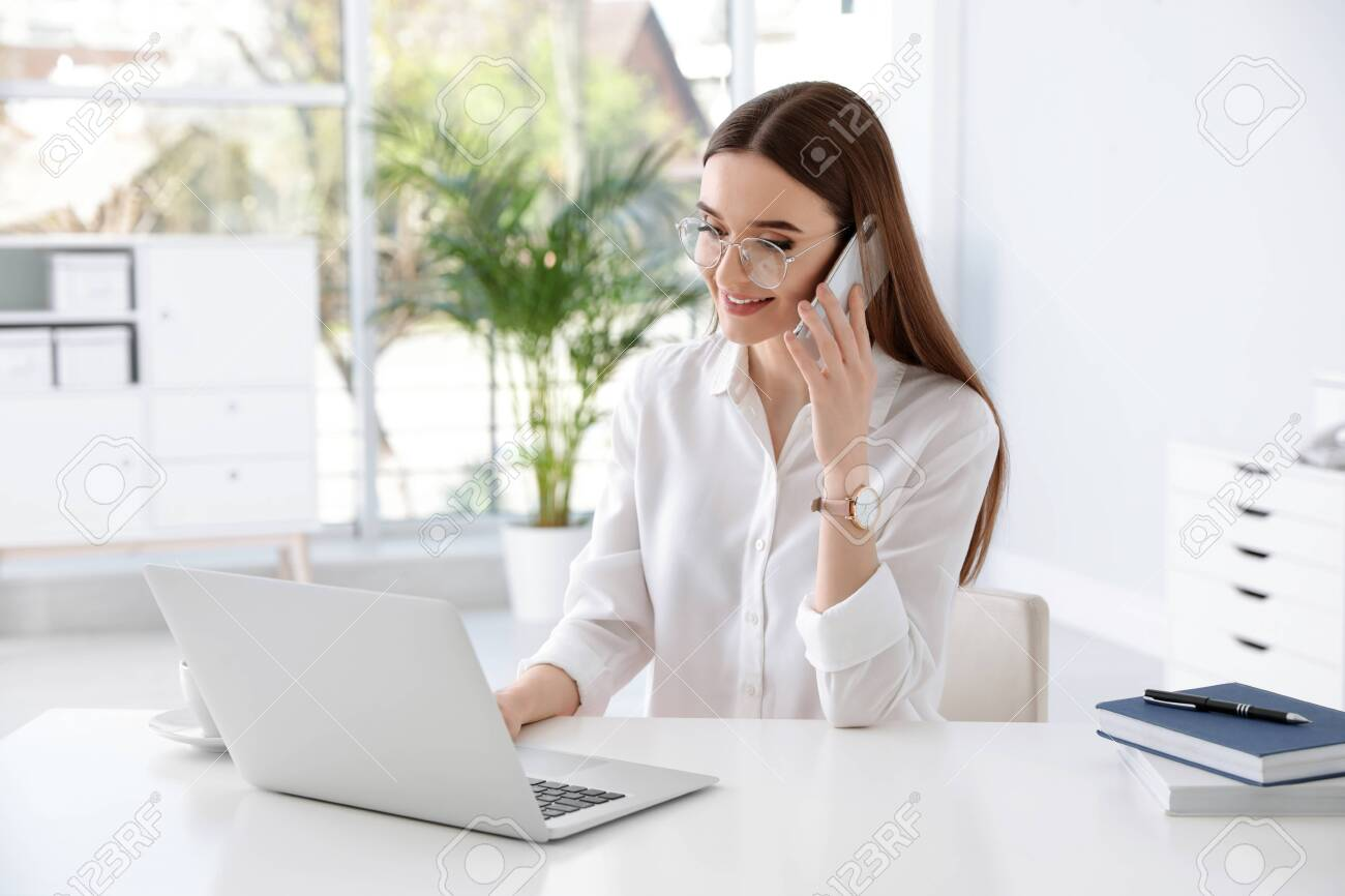 Young businesswoman talking on phone while using laptop at table in office - 133227094