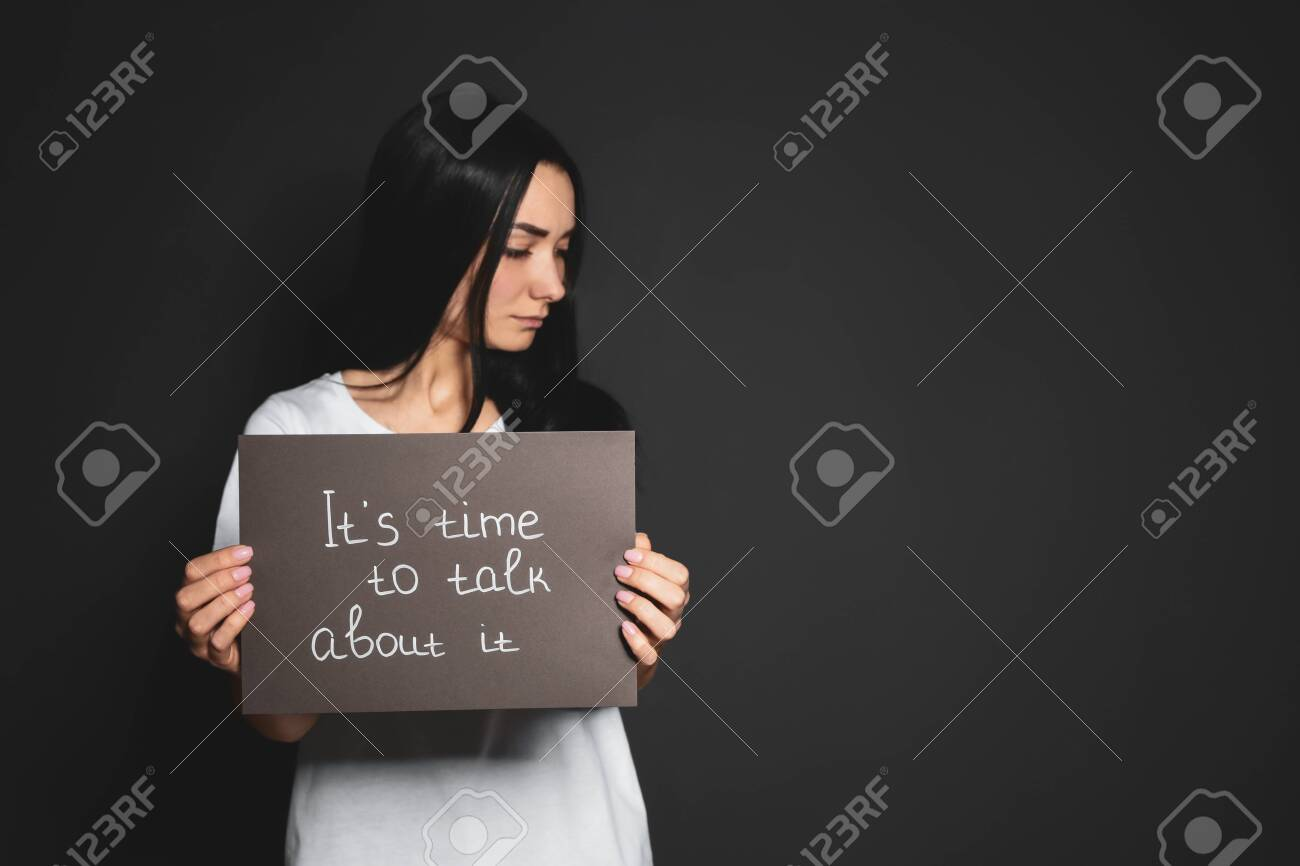 Young woman holding card with words IT'S TIME TO TALK ABOUT IT against dark background. Space for text - 133227134