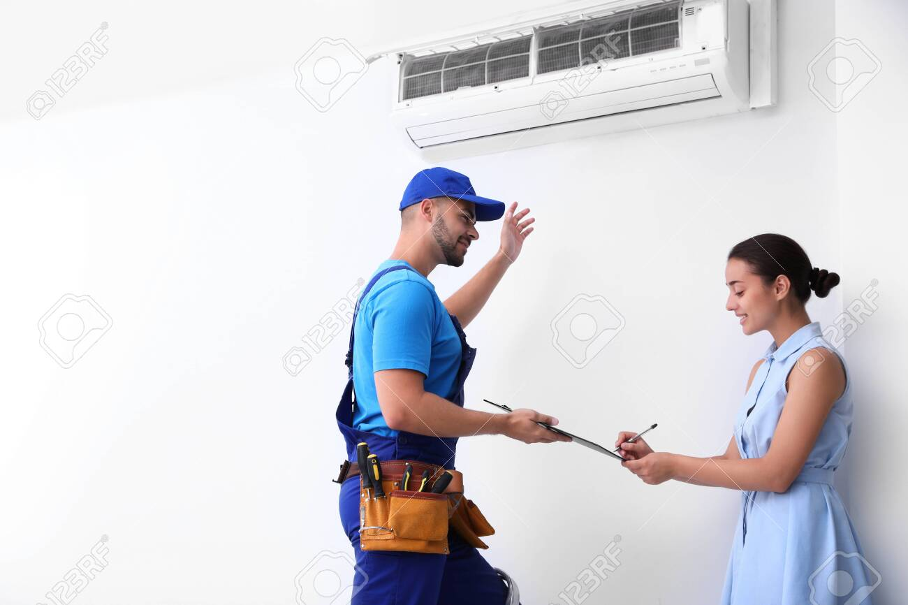 Professional technician speaking with woman about air conditioner indoors - 133478107