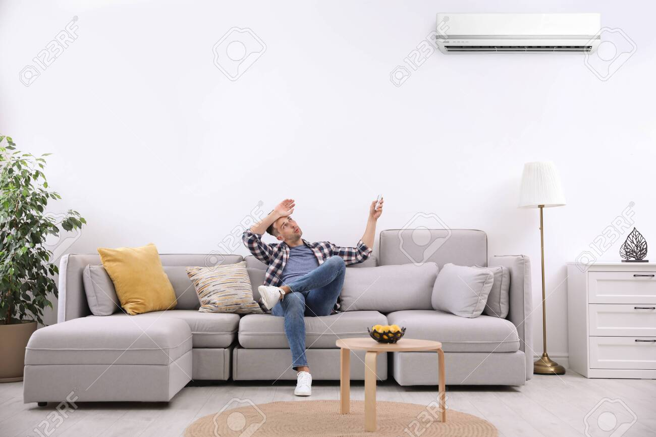 Young man switching on air conditioner with remote control at home - 133697182