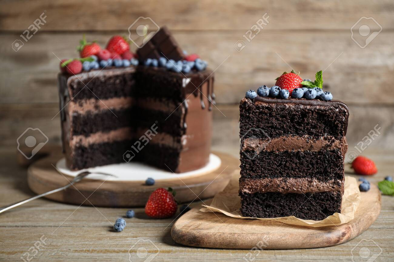 Delicious chocolate cake decorated with fresh berries on wooden table - 133309232