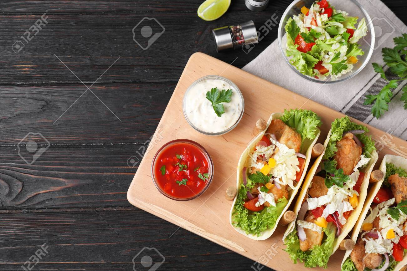 Delicious fish tacos served on dark wooden table, flat lay - 133561160