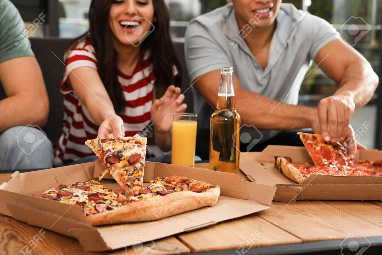 Group of friends having fun party with delicious pizza in cafe, focus on hand - 134236754