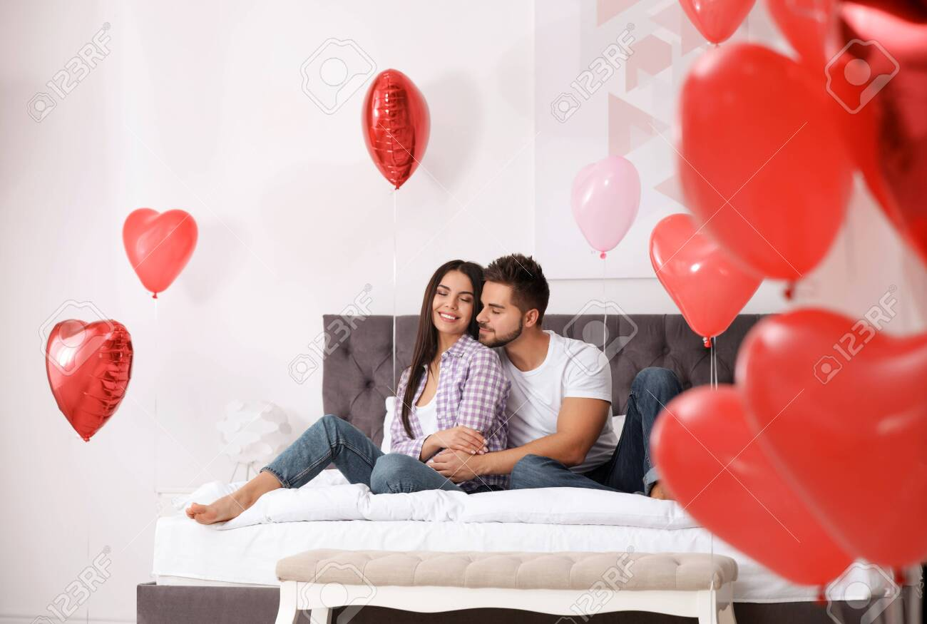 Lovely young couple in bedroom decorated with heart shaped balloons. Valentine's day celebration - 134315794
