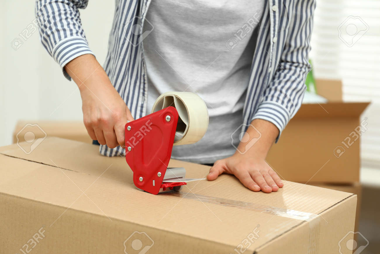 Woman packing cardboard box indoors, closeup. Moving day - 134622464