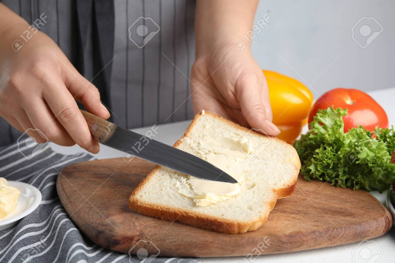 Woman spreading butter on sandwich at white table, closeup - 134842305