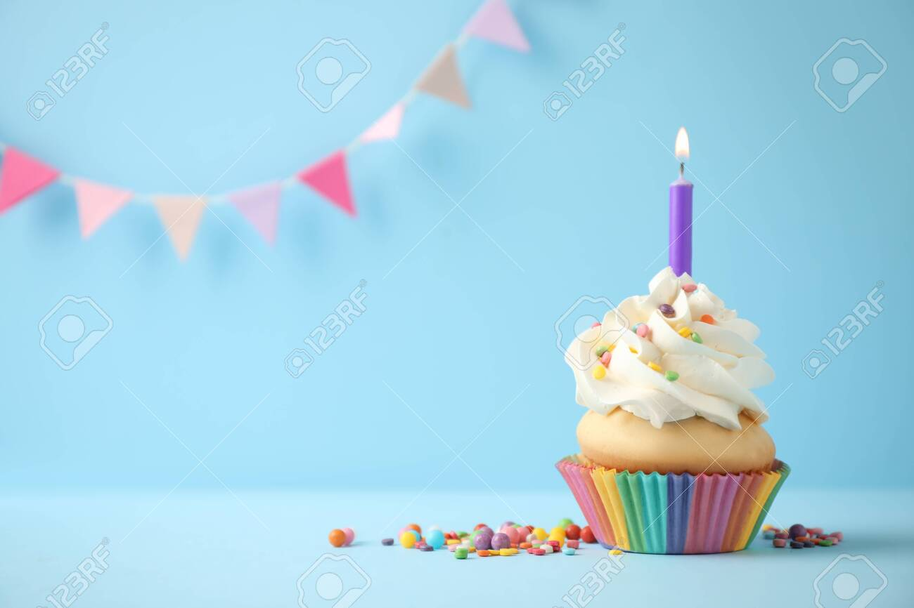 Delicious birthday cupcake with candle on light blue background. Space for text - 135305725