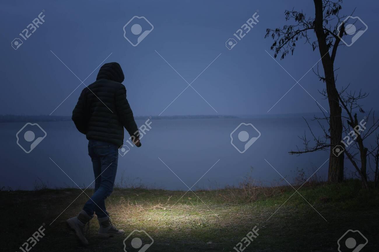 Man with flashlight walking near river in evening - 135644697