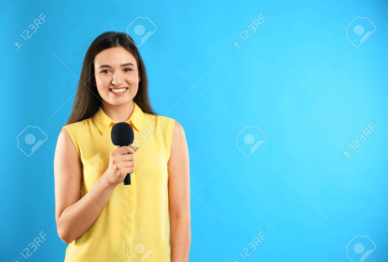 Young female journalist with microphone on blue background. Space for text - 136393429
