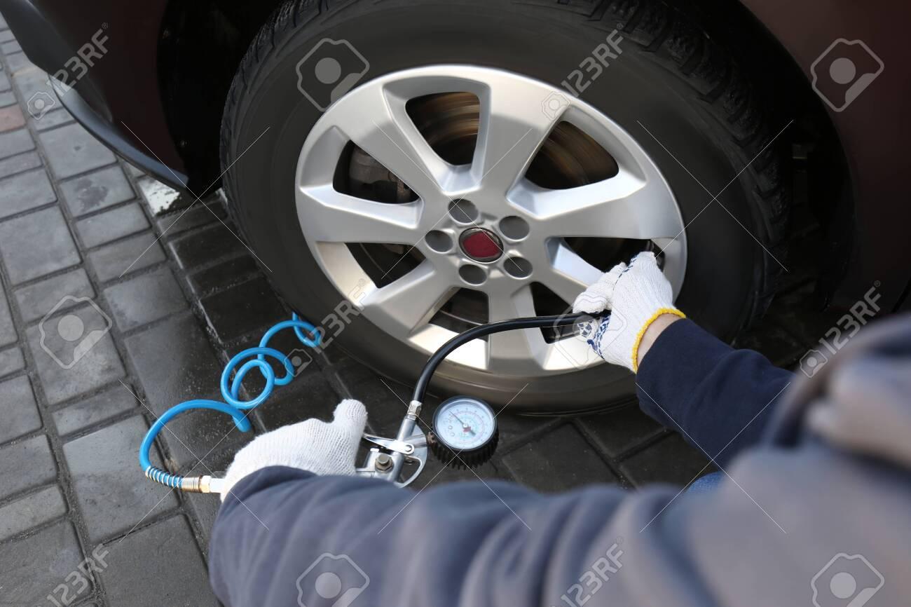 Mechanic checking tire air pressure at car service, closeup - 136378279